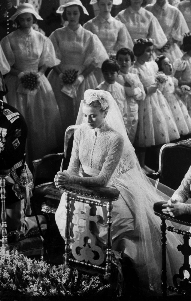 "Grace Kelly prays before her wedding to Prince Rainier III, April 1956. (England's Queen Elizabeth II reportedly refused to attend the wedding because there were ""too many movie stars."")"