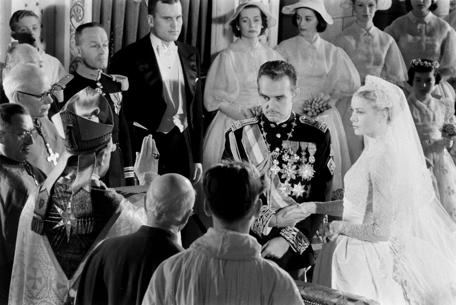Grace Kelly and Prince Rainier join hands as the Bishop of Monaco, Mgr. Gilles Barthe, administers the nuptial benediction at Saint Nicholas Cathedral, April 1956.