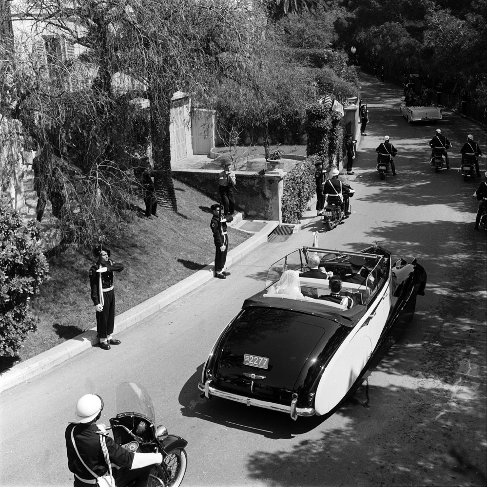Princess Grace and Prince Rainier III, newlyweds, are whisked away in a Rolls Royce convertible, April 1956.