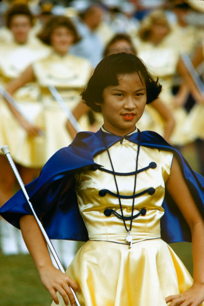 Drum majorette leads band at Honolulu football game, 1959.