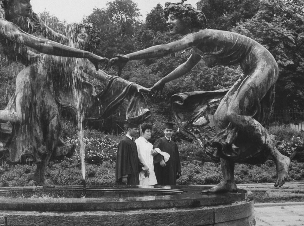 A trio of newly graduated students strolls soberly past a trio of figures dancing ring-around-a-rosy at a fountain.