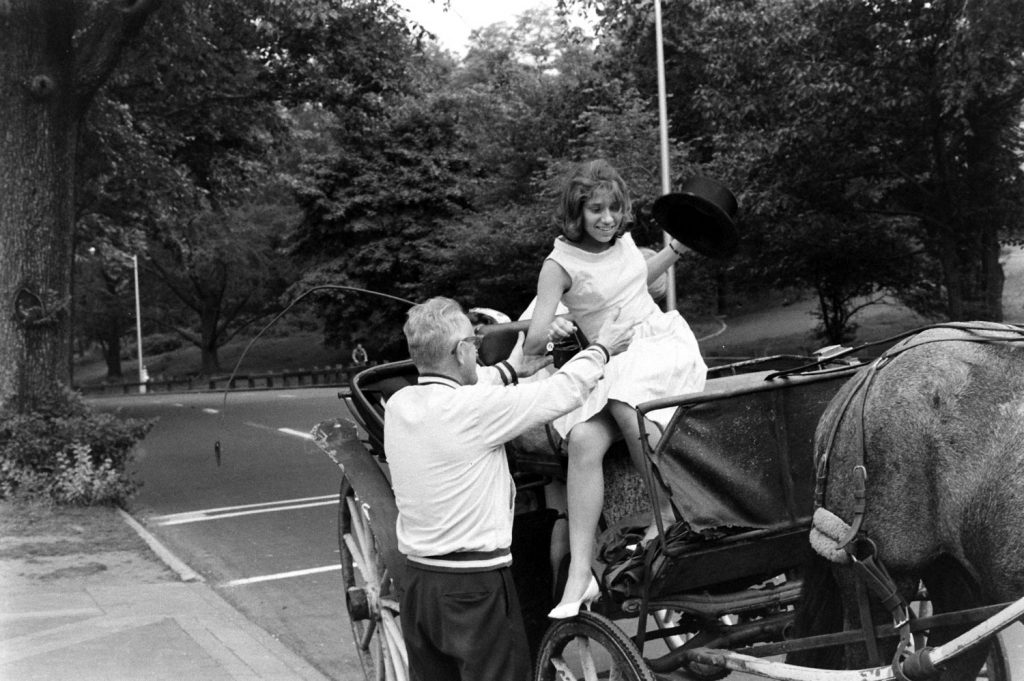 A young woman is helped down from a horse-drawn carriage, Central Park, 1961.