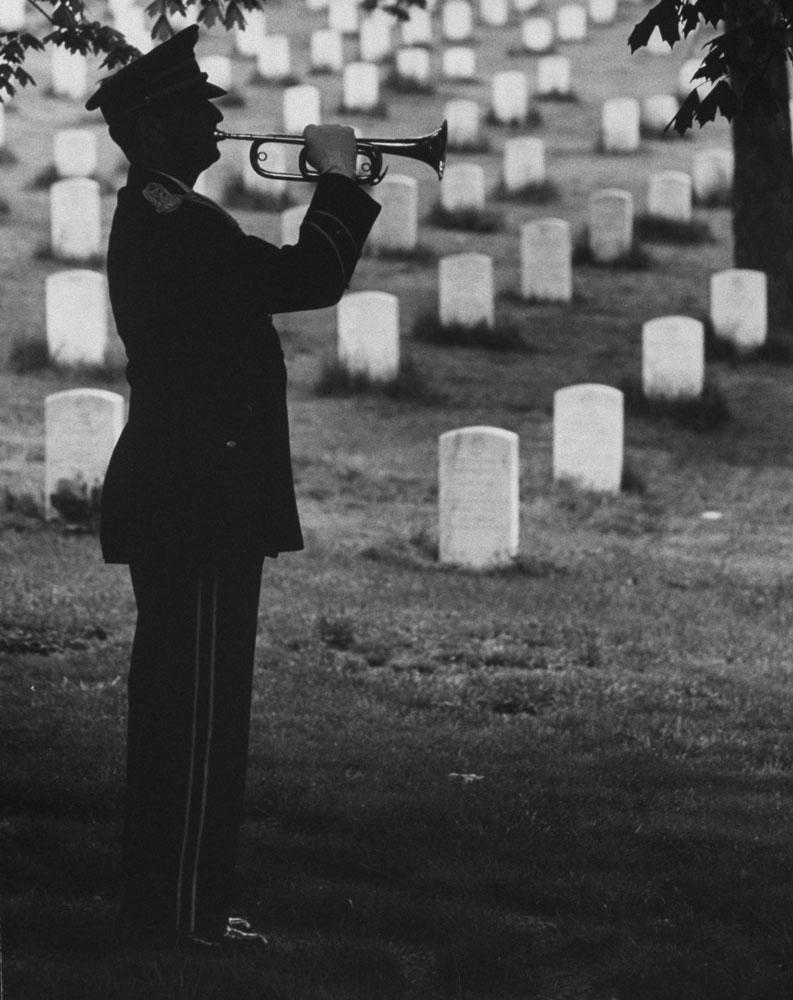 "A bugler plays ""Taps"" at Arlington National Cemetery, 1965."
