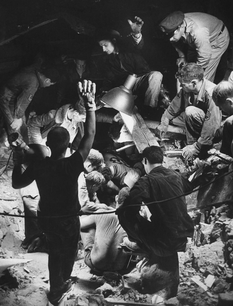 Rescuers attempt to free a woman trapped in rubble, Waco, Texas, May 1965.