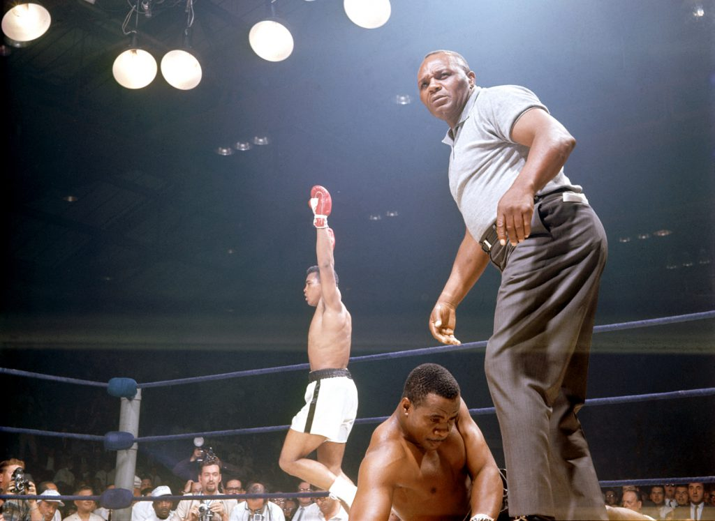 With Sonny Liston lying dazed -- or, as some would have it, pretending to be dazed -- on the canvas, Muhammad Ali exults, May 25, 1965. (Referee is Jersey Joe Walcott.)