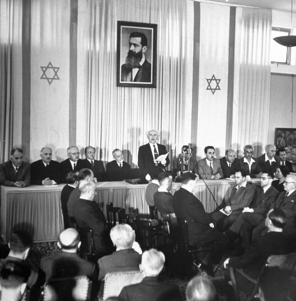 Proclamation of Nationhood is read by Israel's Prime Minister David Ben-Gurion. Around him are members of the provisional government, including Foreign Minister Moshe Shertok (third from right). Labor Minister Moshe Ben Tov (extreme right) wears sport shirt. Portrait above is of Theodor Herzl, Zionism's founder