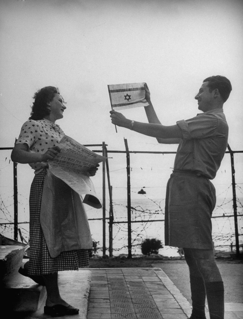 Happily displaying the Israeli flag shortly after the establishment of the state of Israel, exact location unknown, May 1948.