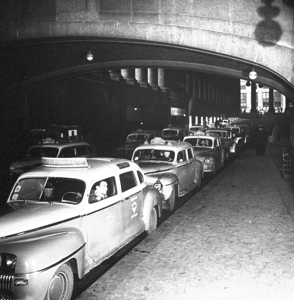 Taxicabs line up for arriving train passengers at (the original) Pennsylvania Station, New York City, 1944.