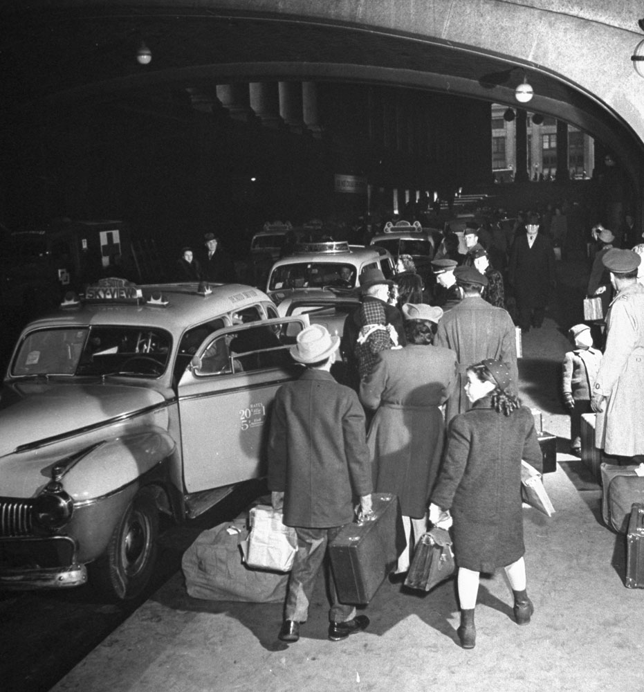 Train passengers wait to take taxi cabs outside (the original) Pennsylvania Station, New York City, 1944.