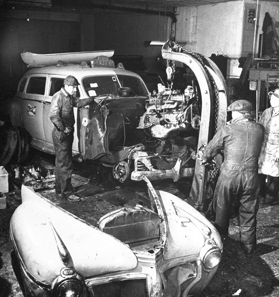 Mechanics use a hoist to drop in the motor of a taxicab under repair at cab company's maintenance garage, NYC, 1944.