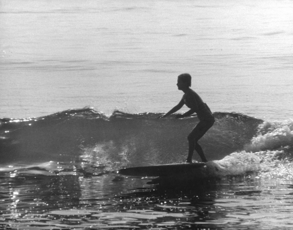 Sixteen-year-old Kathy Kohner (the real-life inspiration for the character of Gidget) rides a wave, Malibu, Calif., 1957.