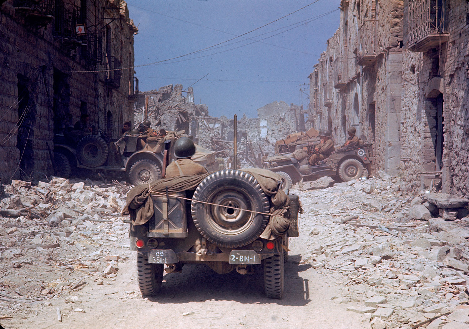 American jeeps travelled through a bombed-out town during the drive towards Rome, World War II.