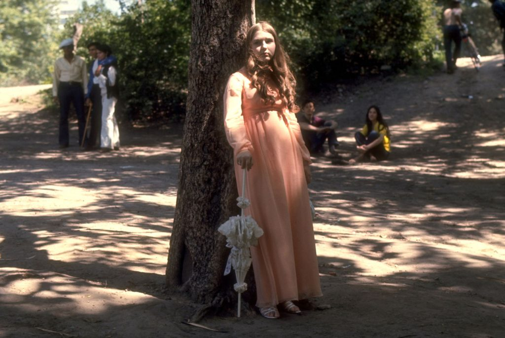 Girl in a pink dress holding a parasol leans against a tree in Central Park, 1969.
