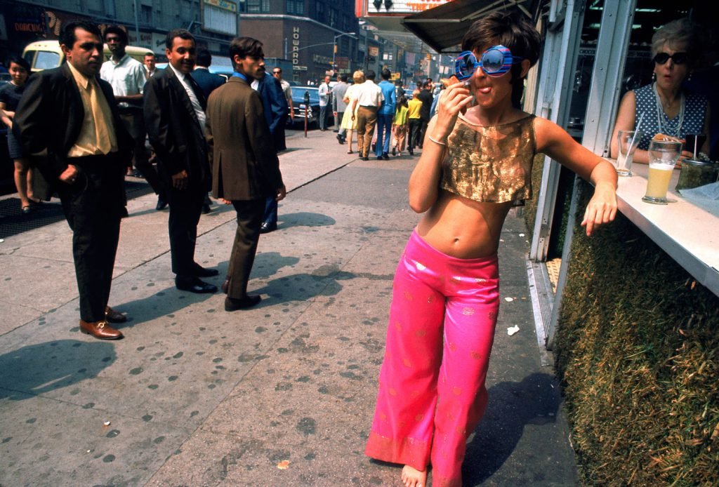 Men ogle a young woman wearing pink pants and a gold top, New York City, summer 1969.