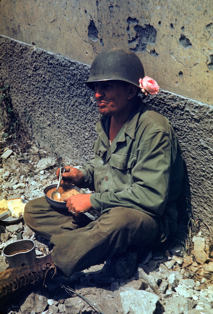 An American soldier on a meal break during the drive towards Rome, 1944.