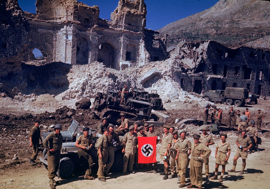 British and South African soldiers hold up a Nazi trophy flag while combat engineers on bulldozers clear a path through the debris of a bombed-out city, Italian Campaign, World War II.
