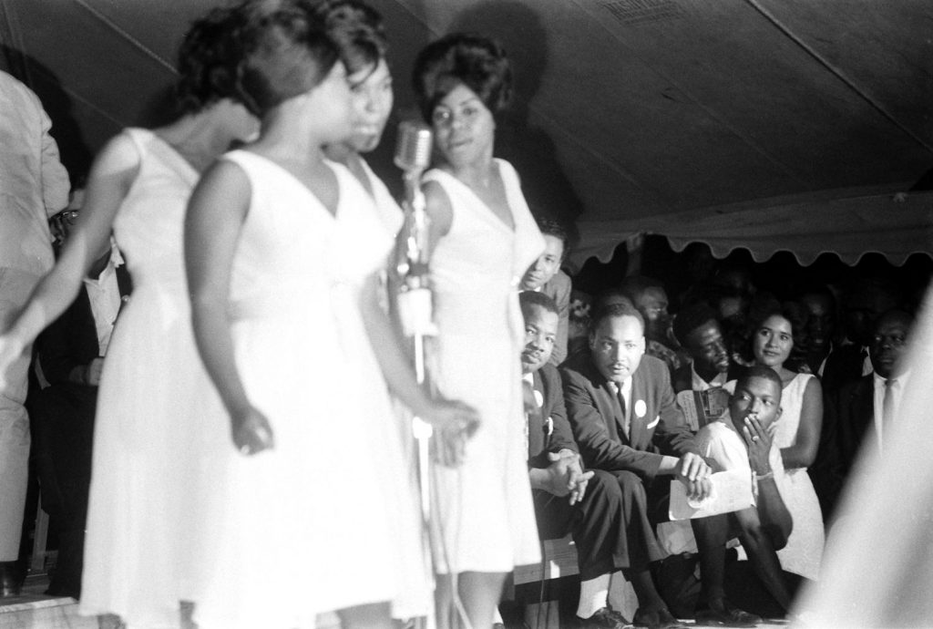 Martin Luther King Jr. (seated, at right) watches the Shirelles perform during the Salute to Freedom benefit concert in Birmingham, Ala., August 5, 1963.