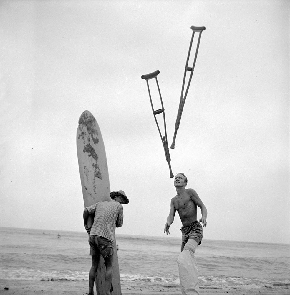 Tossing crutches up on the beach, [surfer] hobbles over to his surfboard and waits for receding wave to wash him out where swells have broken.