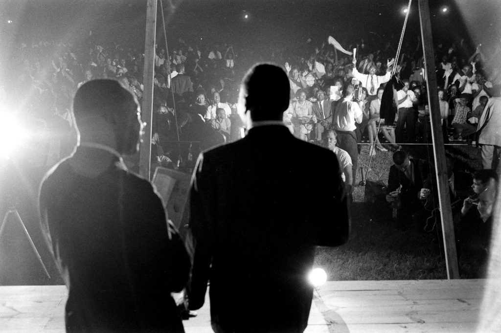 Martin Luther King Jr. (left) and an unidentified man address the crowd during the Salute to Freedom benefit concert in Birmingham, Ala., August 5, 1963.