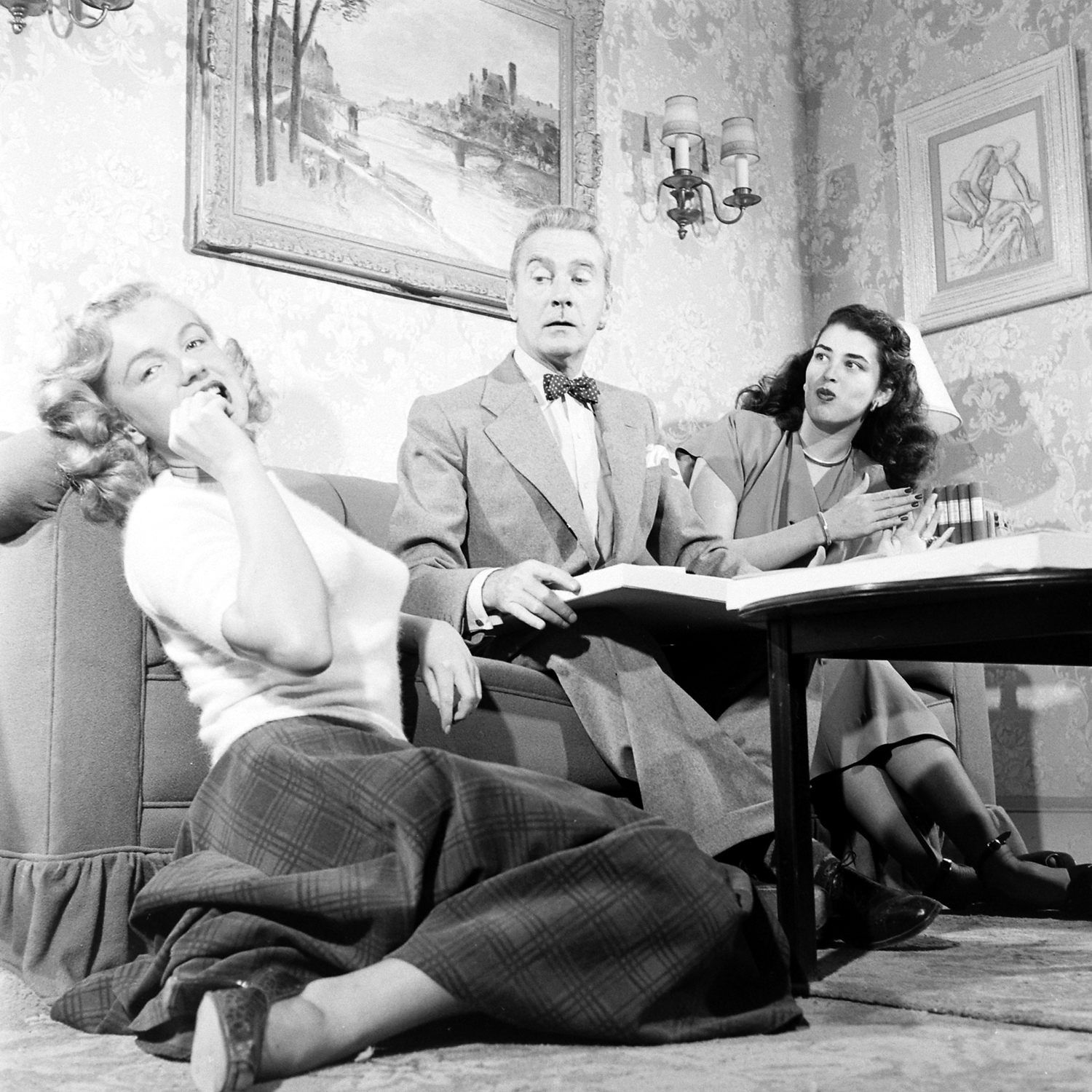 "Then-unknown actress Marilyn Monroe with Clifton Webb and Laurette Luez on the set of a 1948 comedy, ""Sitting Pretty."""