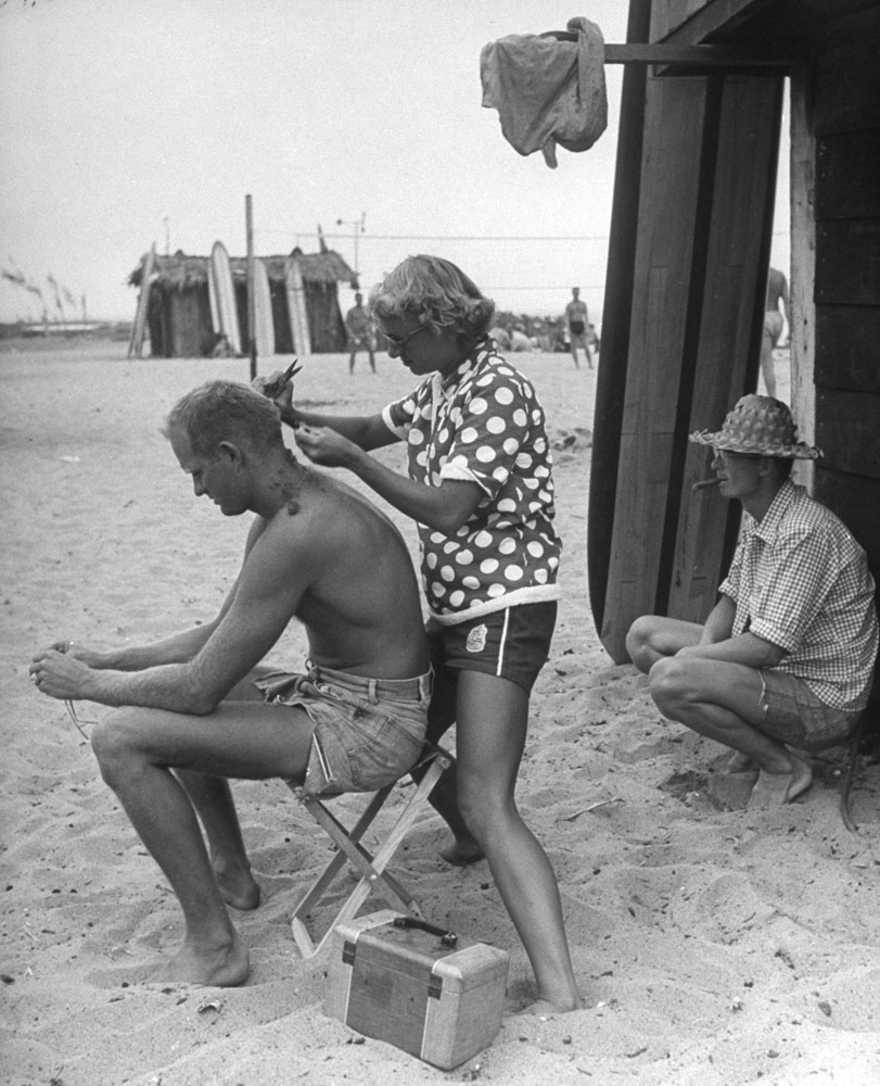 Haircutter to all the beach bums is Myra Roche, mother of three children. She helps friend Warren Miller make ends meet by shearing his hair free.
