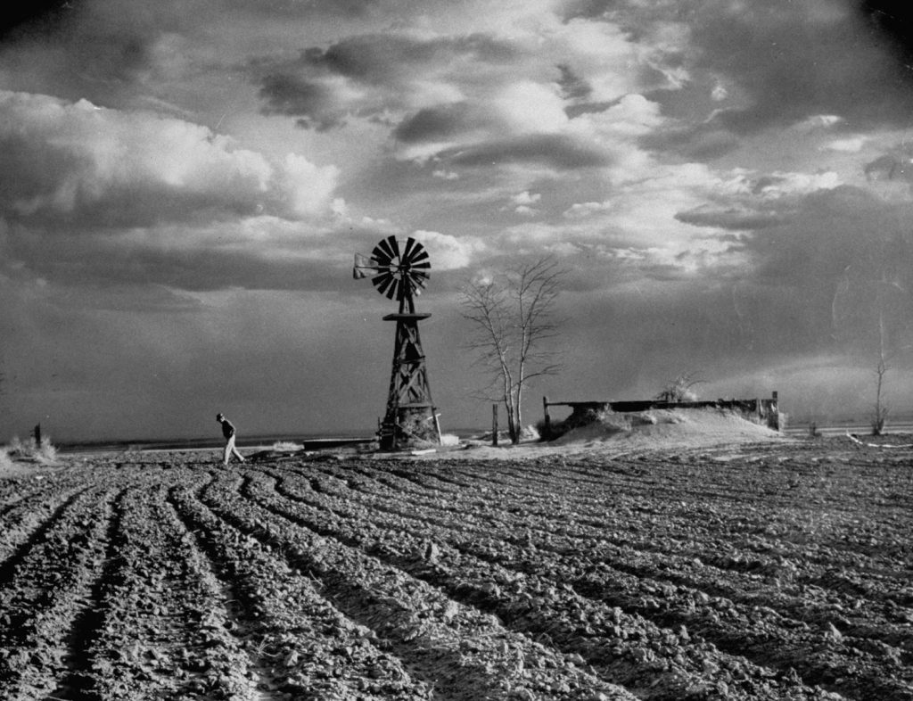 The threatening storm rises above a farm near Hartman, Colo. Once range land, it lies almost ruined by wheat. Dust-choked corral and pump are land's tombstones.