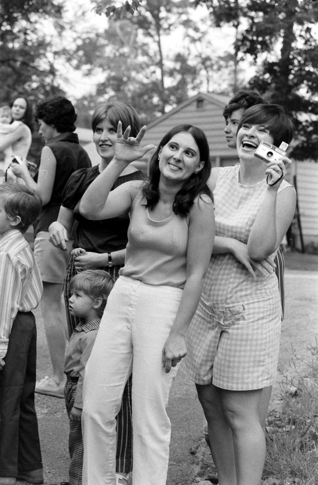 Moms wave to their kids at a school bus stop, New Jersey, 1971
