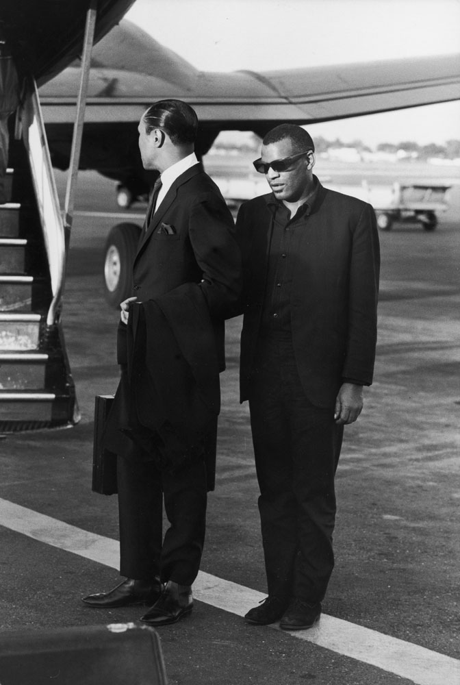 In the early morning at Los Angeles airport, [Ray Charles] waits with his manager, Joe Adams, to board his plane for a flight to New York. His arm is linked to Adams', but Ray still stands very much alone.