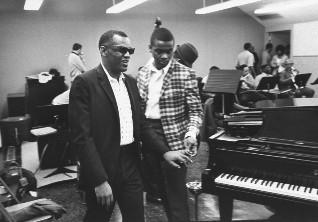 His chauffeur, Vernon Troupe, leads Ray Charles to the piano in Los Angeles studio where Charles records for his own company, named Tangerine after his favorite fruit.