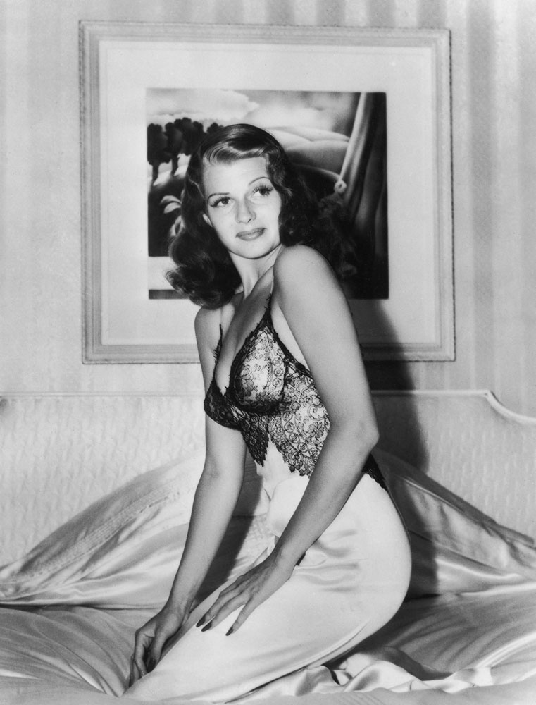 """Rita Hayworth poses """"on her own bed in her own home"""" (as LIFE magazine put it), 1941."""