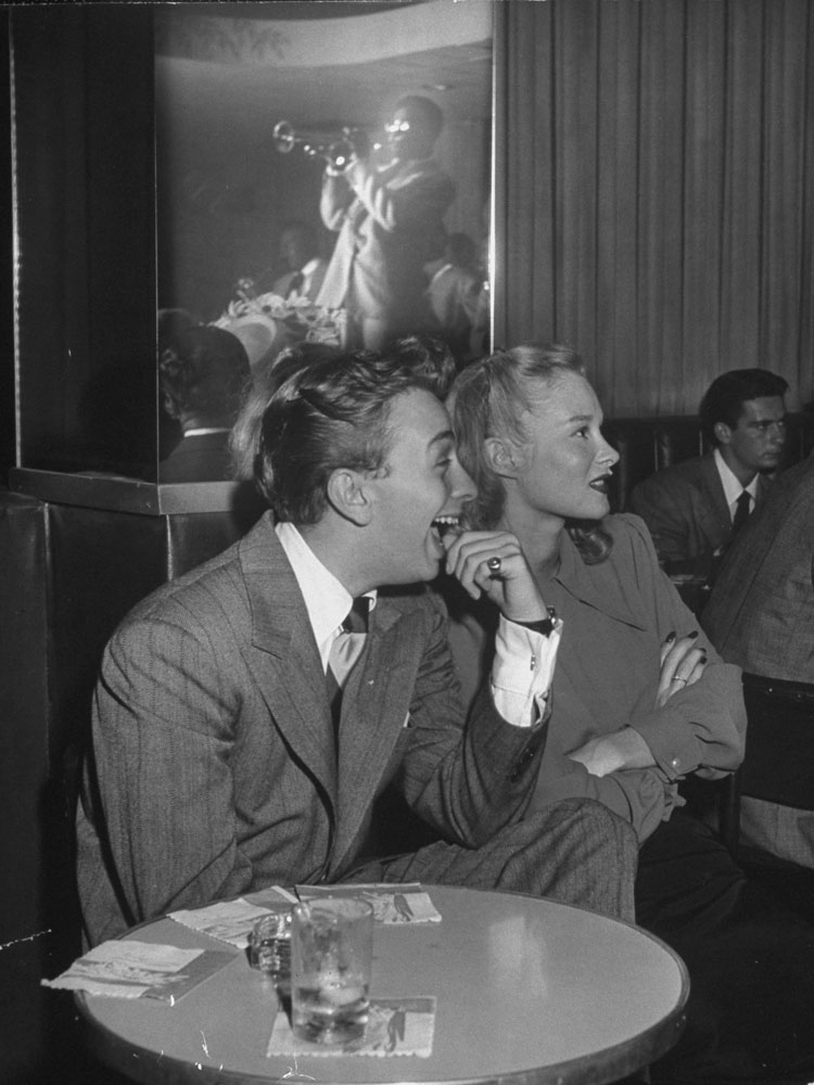 Crooner Mel (Velvet Fog) Torme happily bites on his finger while he and a model, June Bright, dig Dizzy Gillespie (reflected in mirror).