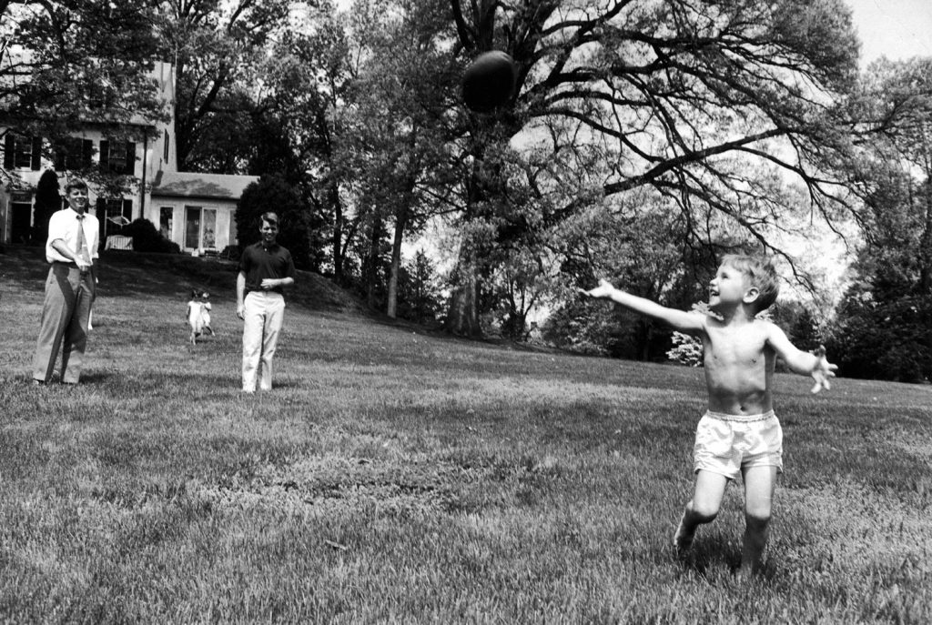 Sen. John Kennedy plays football with his nephew, Bobby Jr., at his brother Robert's Hickory Hill, Va., home, 1957.