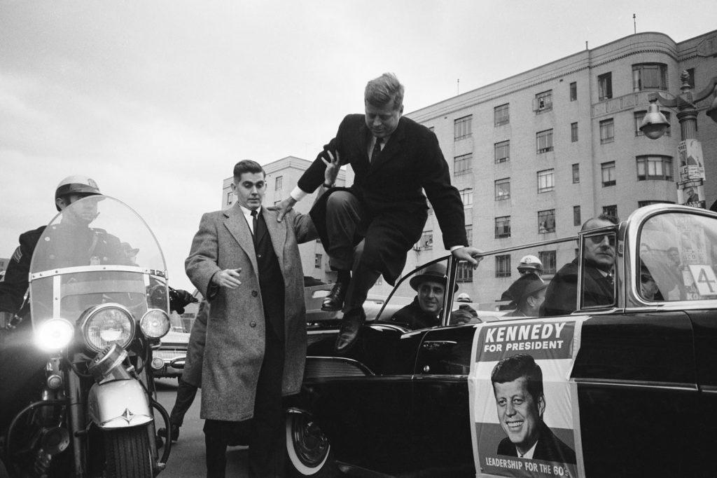 Presidential candidate John F. Kennedy leaps from a car while campaigning, 1960.