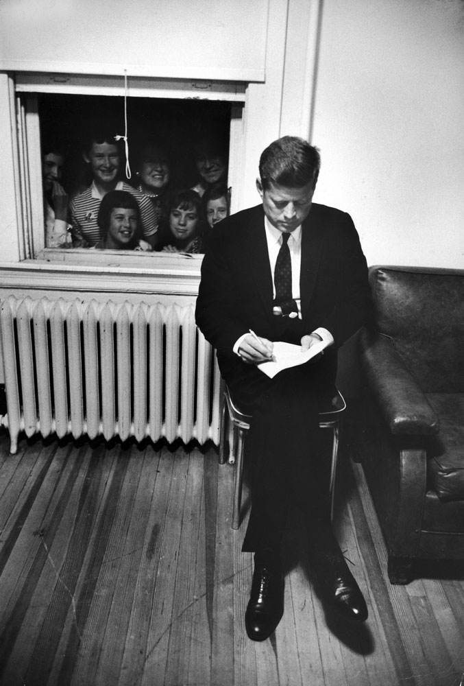 Senator John F. Kennedy checks over a speech at a stop during his presidential campaign, 1960.
