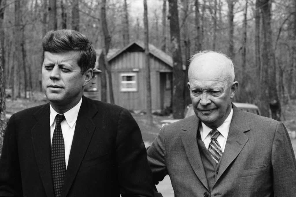 President John F. Kennedy meets with former President Dwight Eisenhower at Camp David in the midst of the Bay of Pigs crisis, 1961.