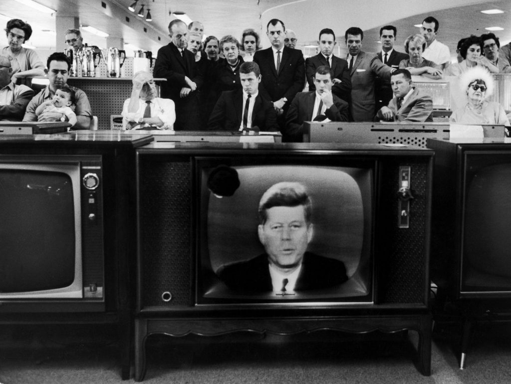 People in a department store watch as President John Kennedy announces a blockade of Cuba during the Cuban Missile Crisis, 1962.
