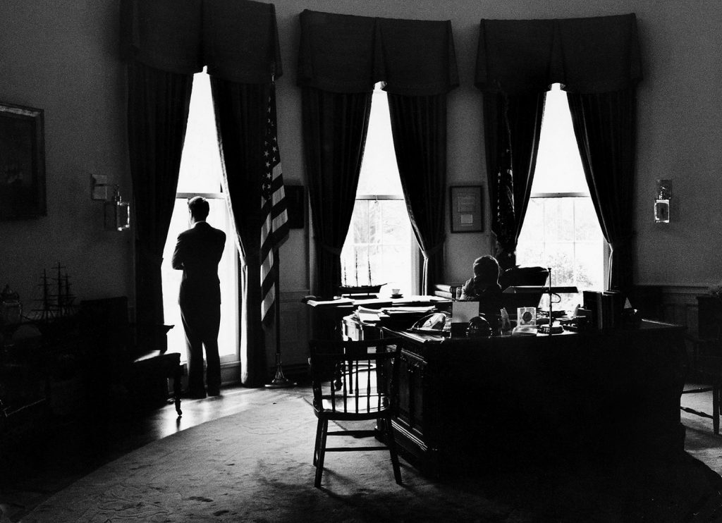President John Kennedy and Attorney General Robert Kennedy (standing at window) in the Oval Office, 1962.
