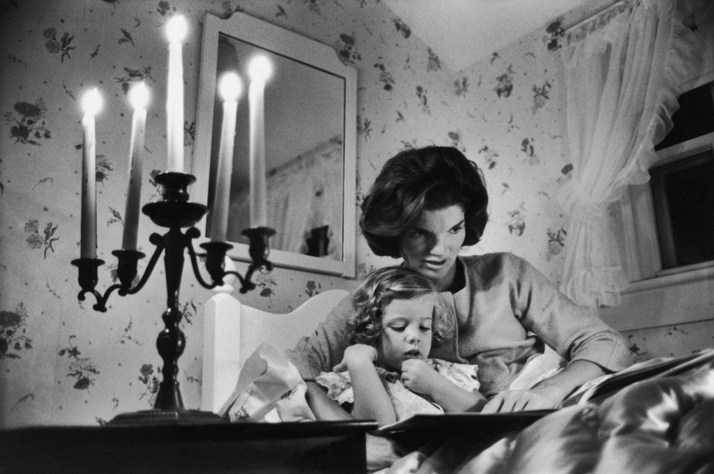 Jackie Kennedy reads to her daughter Caroline at the Kennedy family home in Hyannis Port, Mass., 1960.