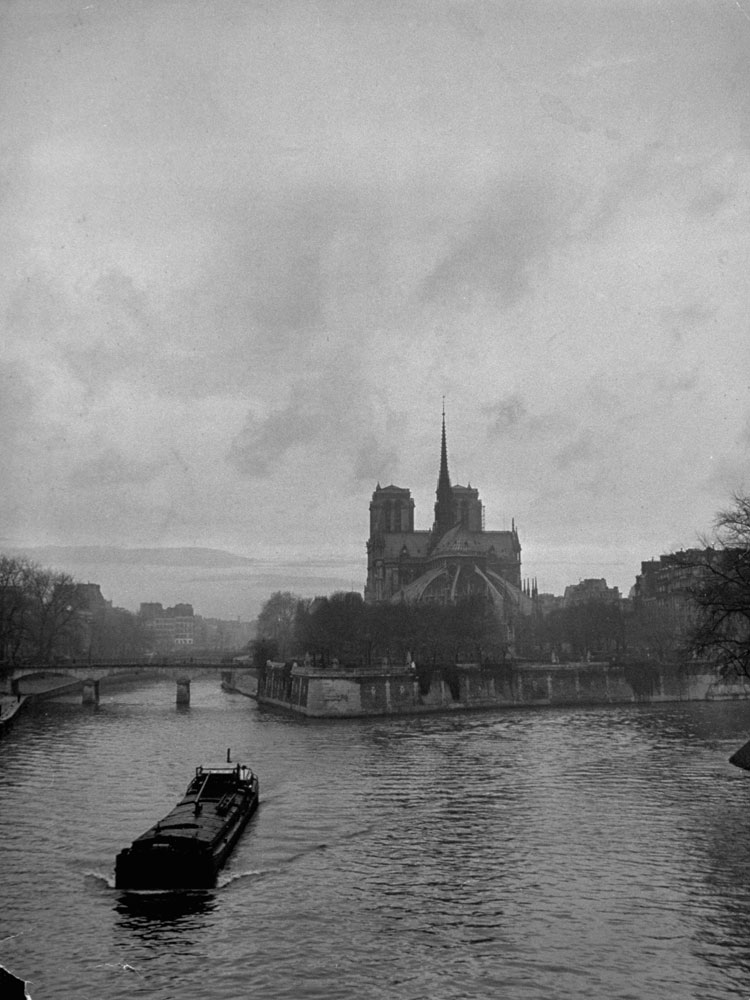 A barge churns up the Seine past Notre Dame on a gloomy winter day in 1946.