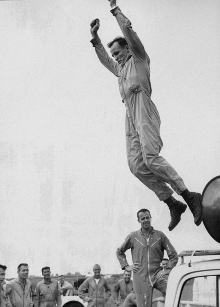 Astronaut Ed White leaps off a truck before an attentive audience of his fellow astronauts during a training exercise, 1963.
