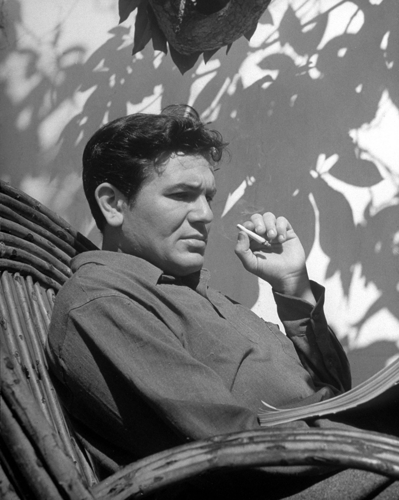 Actor John Garfield smokes and studies the script for the movie, 'They Made Me a Criminal.'