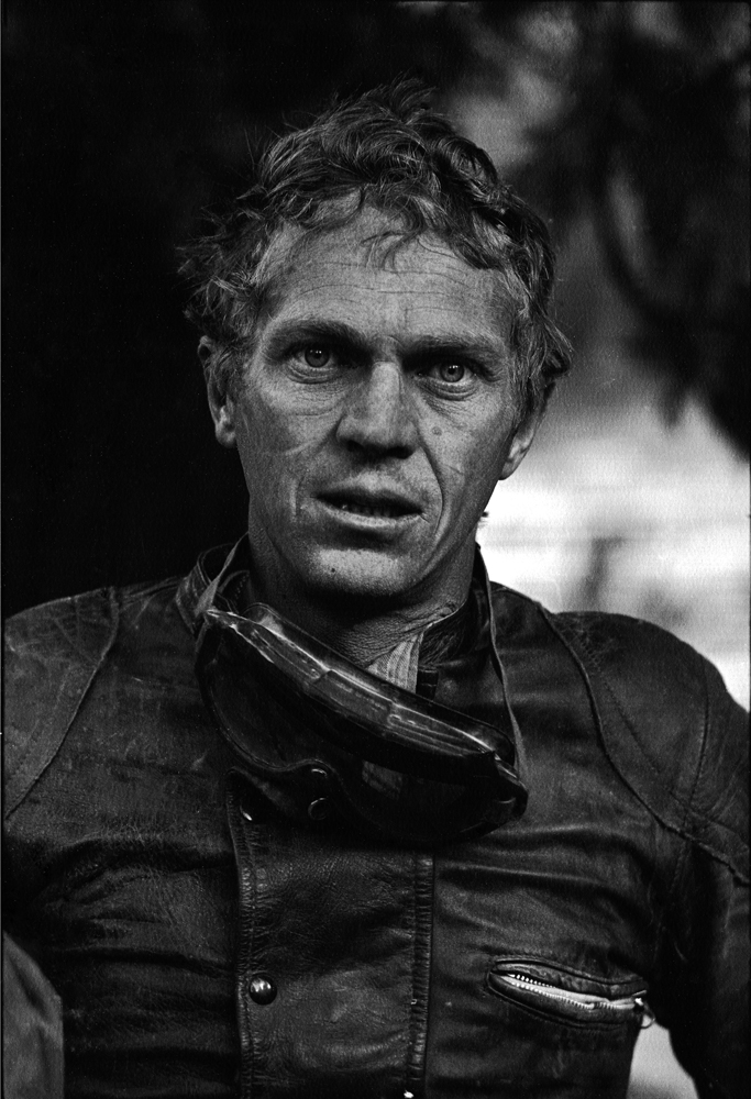 Steve McQueen rests in the midst of a long-distance motorcycle race, 1963.