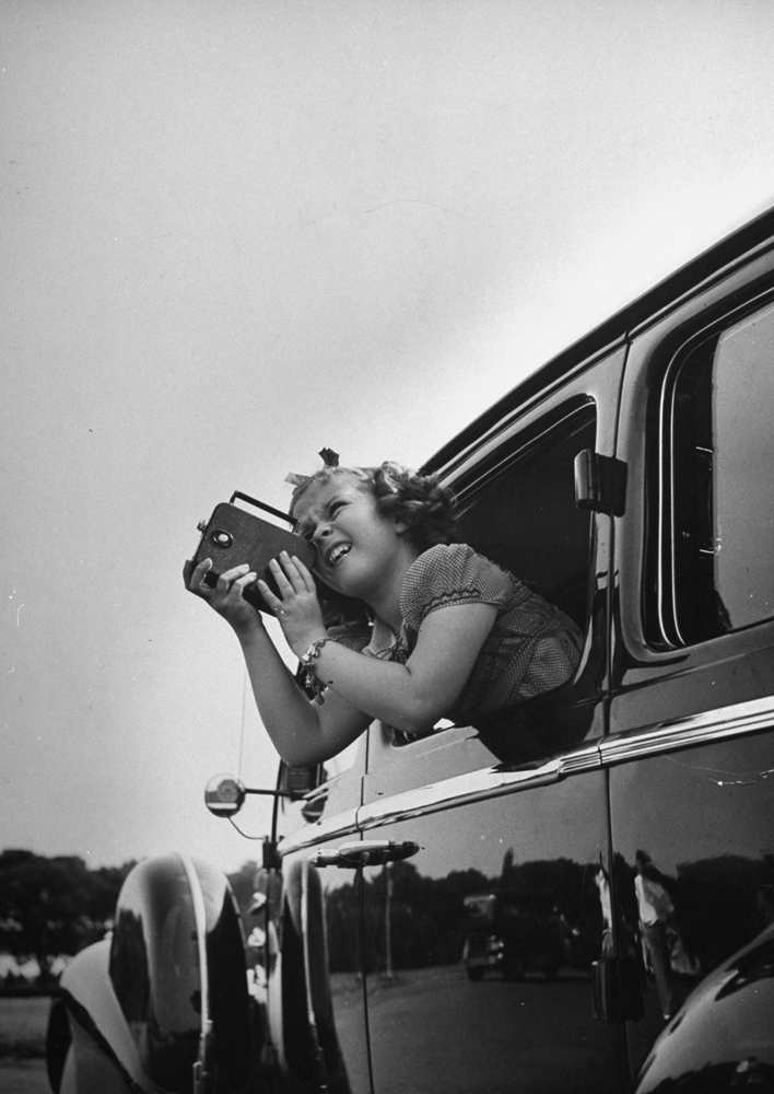Shirley Temple taking pictures of famous sites in Washington, DC, from the window of a car, 1938.