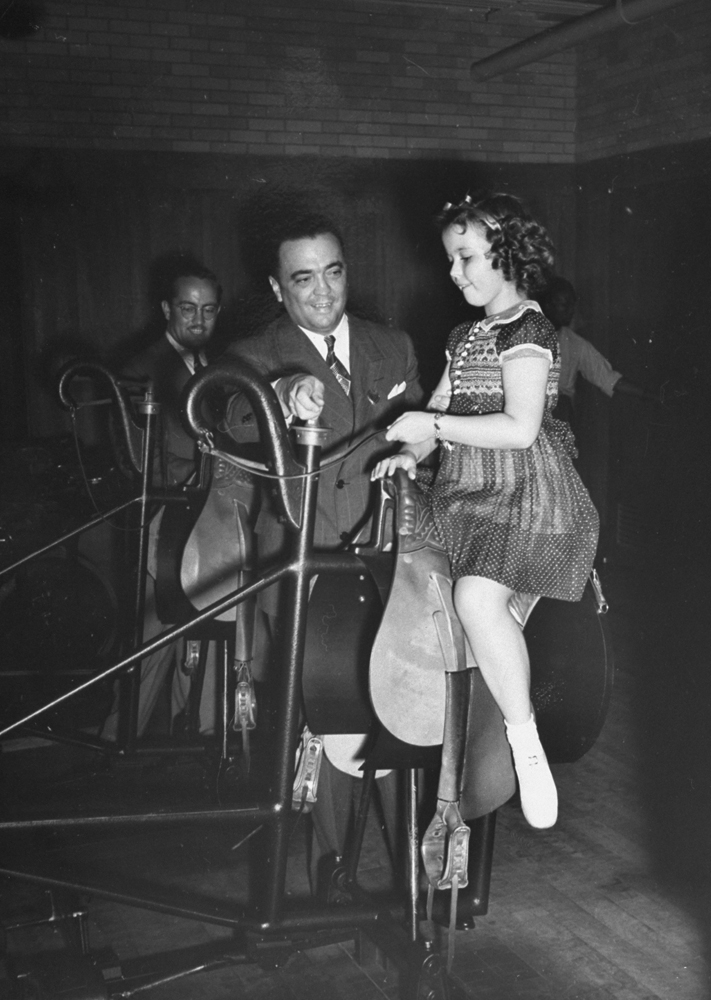 Federal Bureau of Investigation director J. Edgar Hoover shows Shirley Temple how to ride a mechanical horse, 1938.
