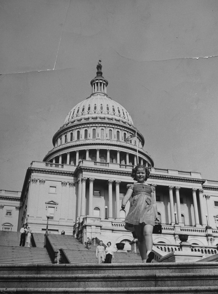 Shirley Temple walking on steps of the U.S. Capitol.
