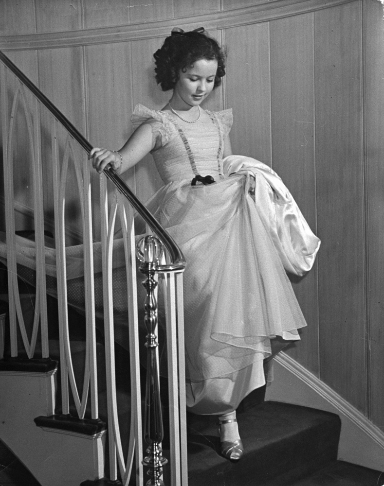 Shirley Temple walks down stairs at the Bel Air Country Club at her 11th birthday party, 1939.