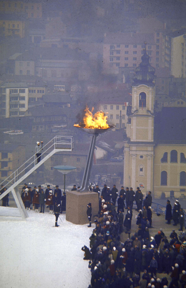 Austrian alpine skier Josl Rieder stands on stair having just lit the Olympic flame at the opening ceremonies of the 1964 Winter Olympics.