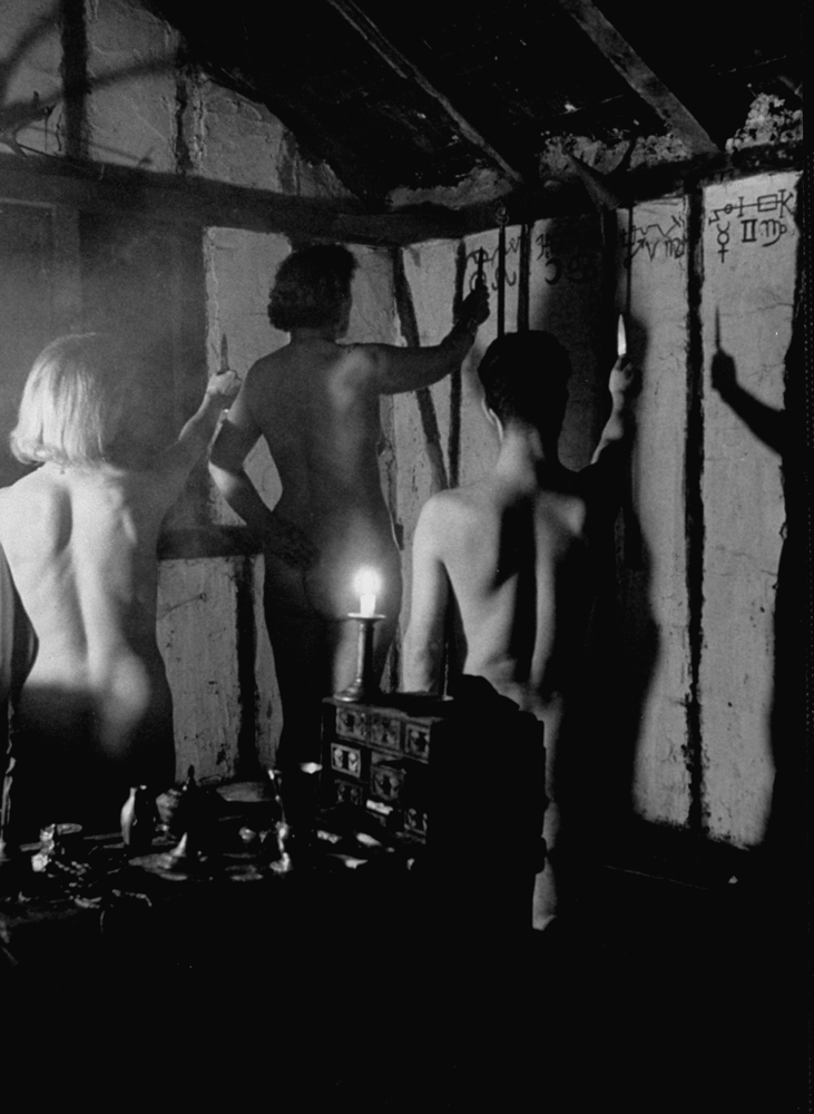 Beneath cabalistic symbols, nude witches raise ritual knives to invoke their gods at a meeting. Their nakedness outrages many people, but witches claim this represents the putting aside of worldly things.