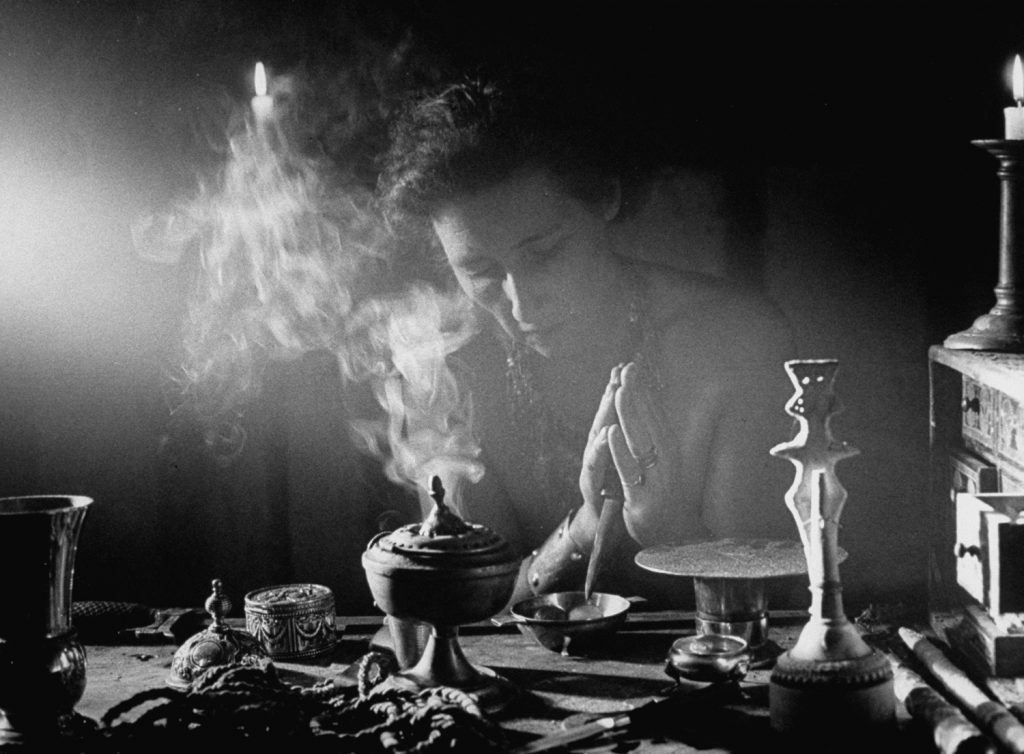 High priestess Artemis stirs salt and water mixture which is used to 'purify' the sacred circle in all witchcraft rites. On the table are incense burner, cord and statue of goddess. At right is herb chest containing incense.