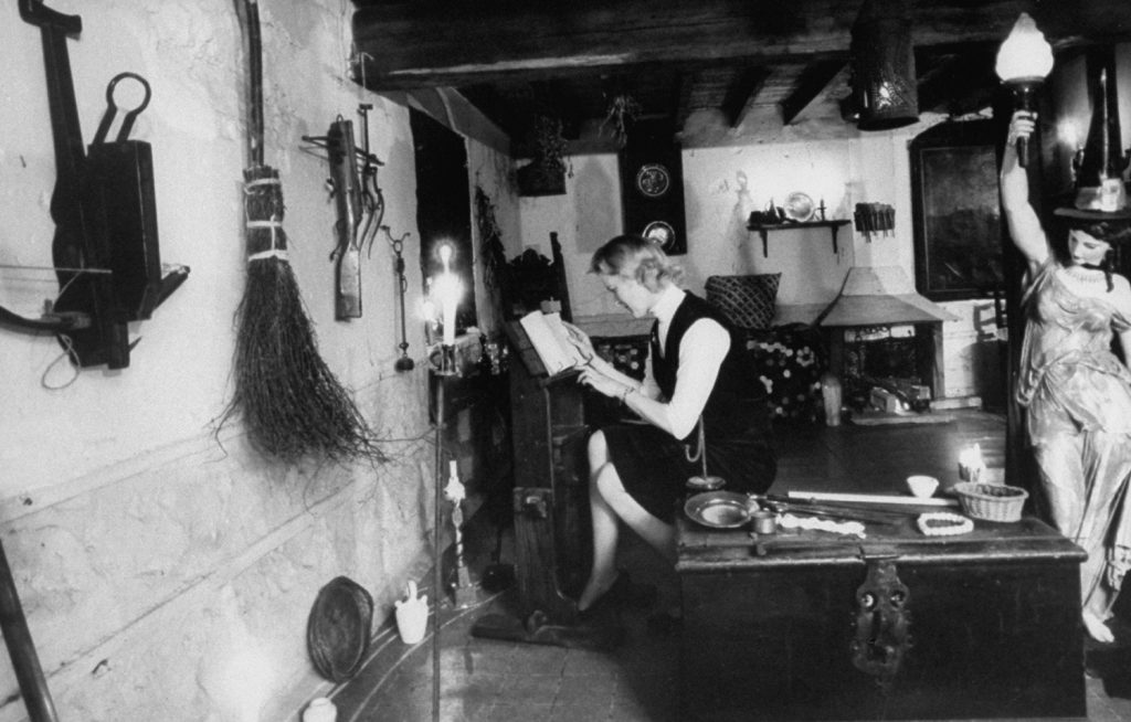 A witch studying in a museum, England, 1964.